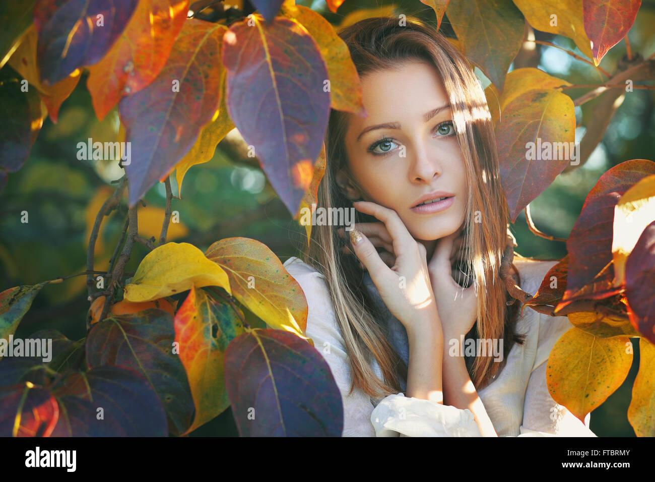 Hermosa mujer joven posando entre coloridas hojas de otoño Foto de stock