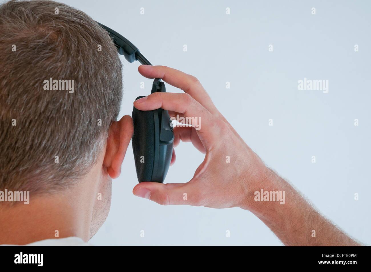 El hombre toma su auricular apagado. Cerrar vista. Imagen De Stock