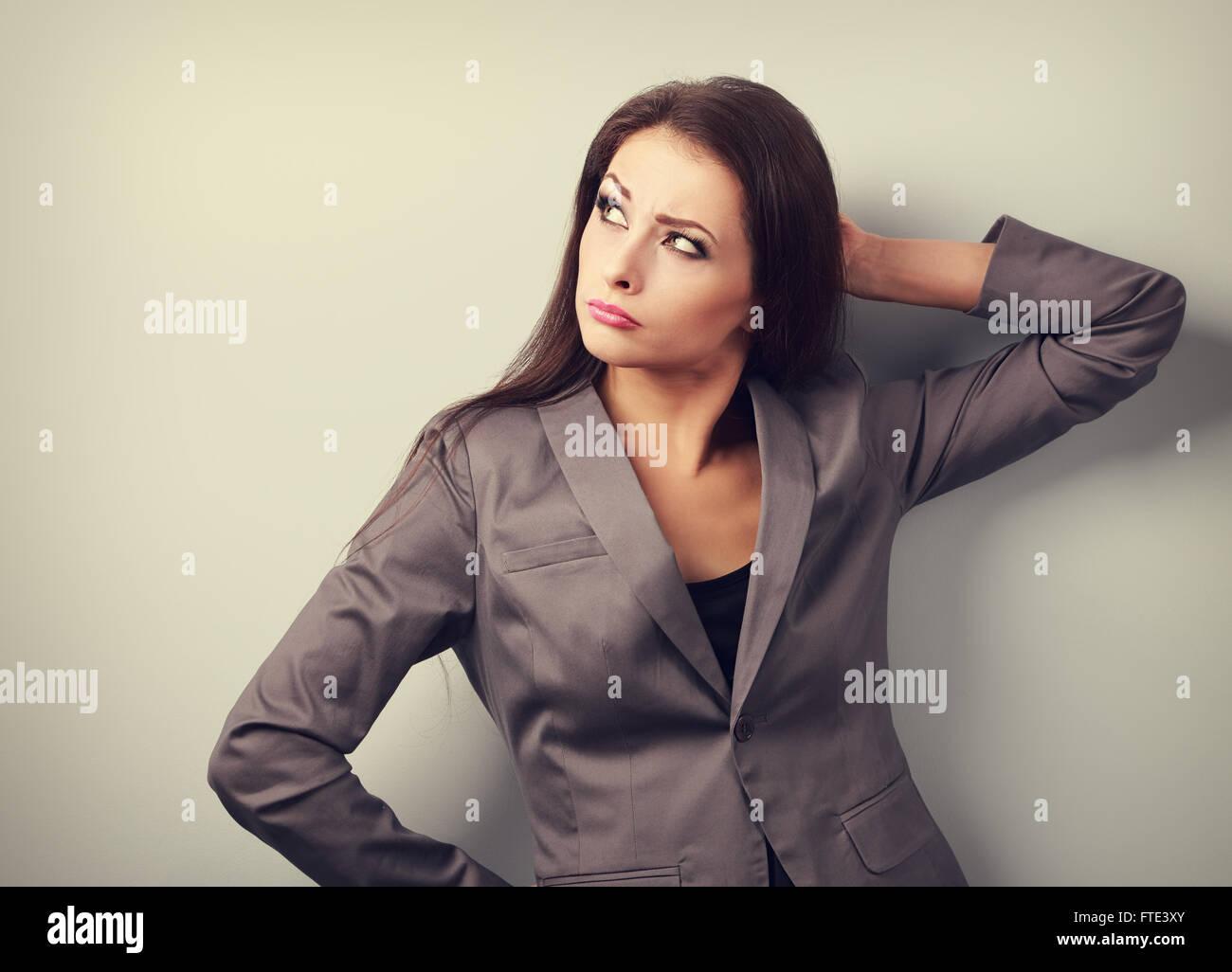Concentración molesta mujer de negocios en traje buscando tonos upю retrato Foto de stock