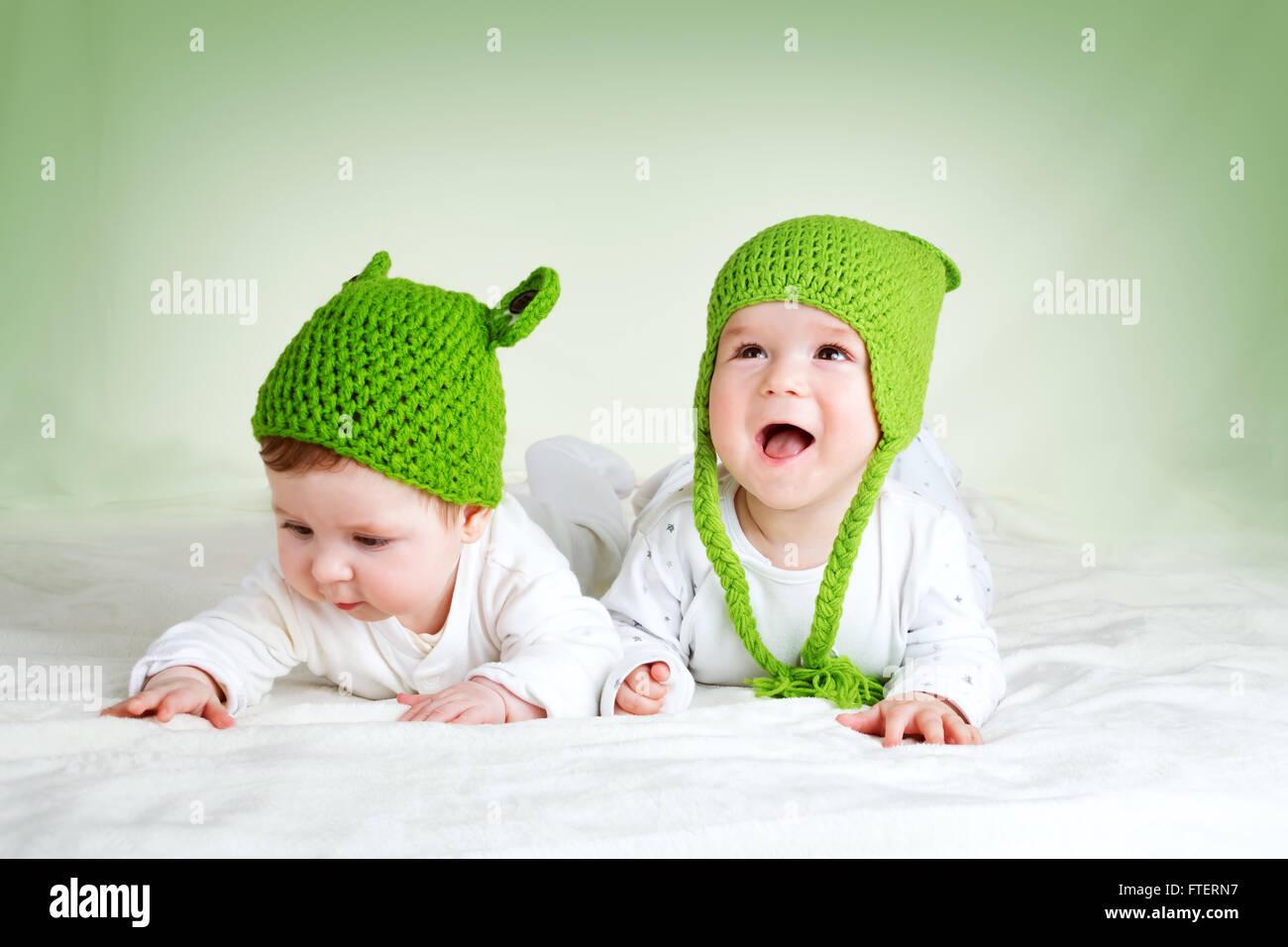 Dos lindos bebés acostado en rana en Manta spft sombreros Foto de stock