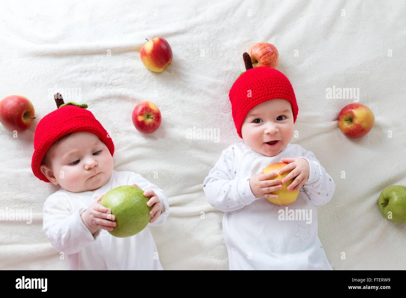 Dos lindos bebés acostado en sombreros en Manta suave con manzanas Foto de stock