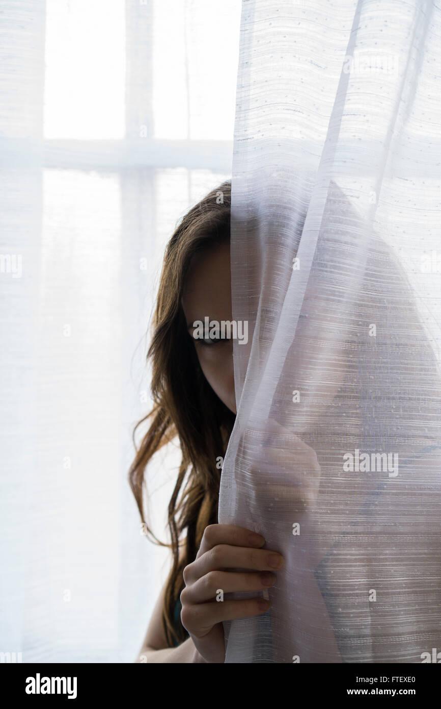 Grave joven escondiéndose detrás de las cortinas de la ventana Foto de stock
