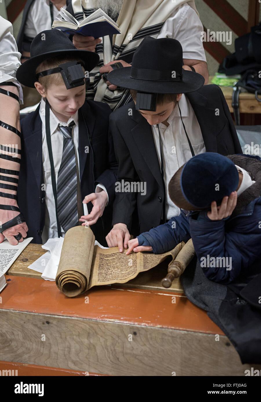 Los adolescentes judíos religiosos escuchar la lectura de la Megillah en Purim en una sinagoga en Brooklyn, Imagen De Stock