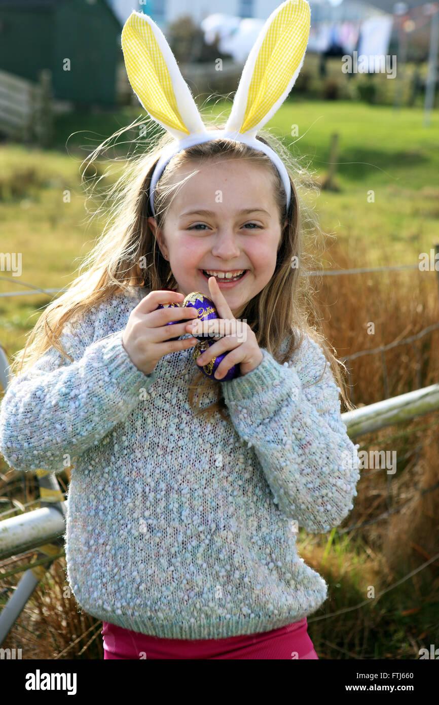 Orejas de conejo en una niña de siete años, mientras que en una búsqueda del huevo de pascua Foto de stock