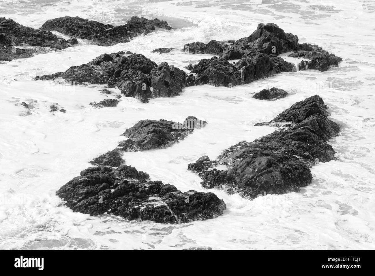 Rocas Negras en blanco Surf Imagen De Stock