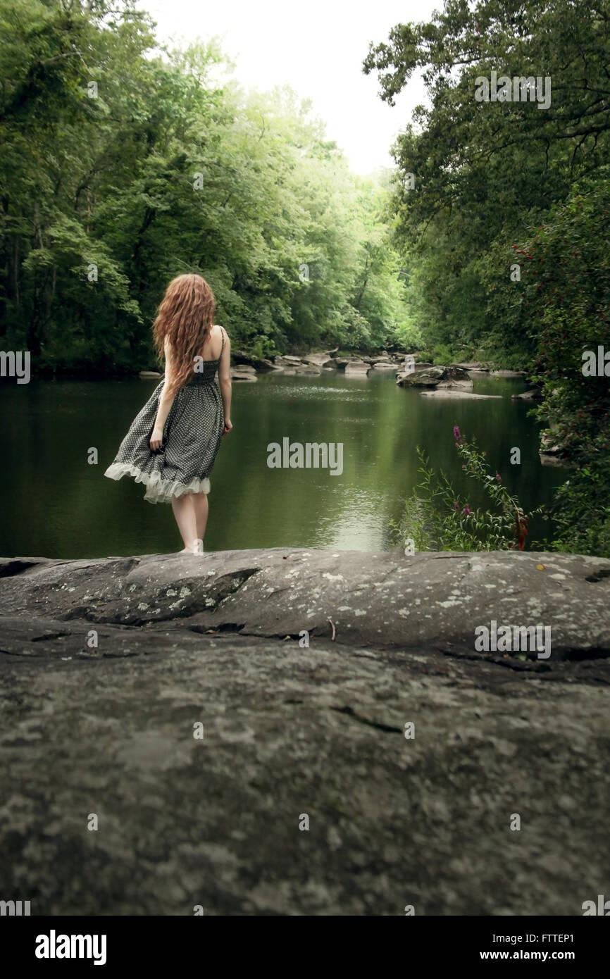 Mujer en largos vestidos de Sun en el lago Imagen De Stock
