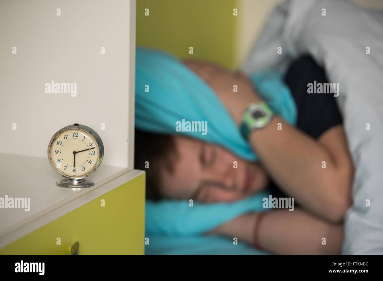 Chico en la cama cubriendo sus oídos mientras suena la alarma Foto de stock