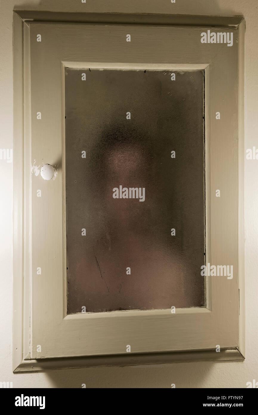 El hombre se enfrenta a su imagen en el espejo turbio. Imagen De Stock