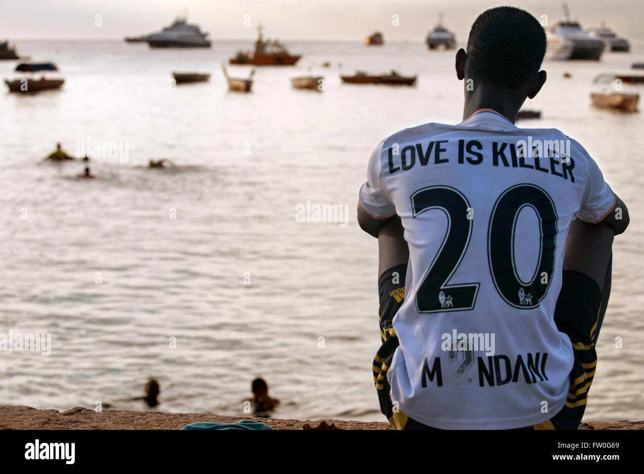 Chico local mira a los pescadores en el Malecón junto al muelle en Stone Town, en Zanzíbar, Tanzania Imagen De Stock