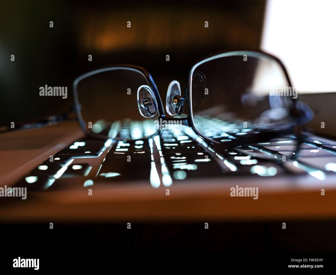 Gafas de lectura de un teclado de portátil de elegancia, profundidad de campo Foto de stock
