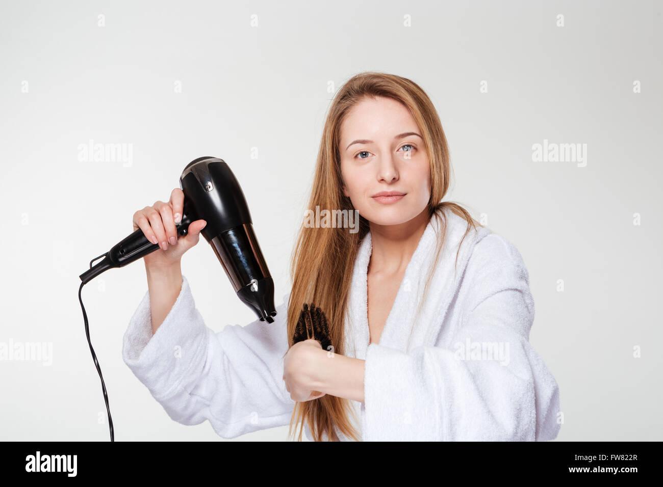 Bella mujer secar su cabello aislado sobre un fondo blanco. Imagen De Stock