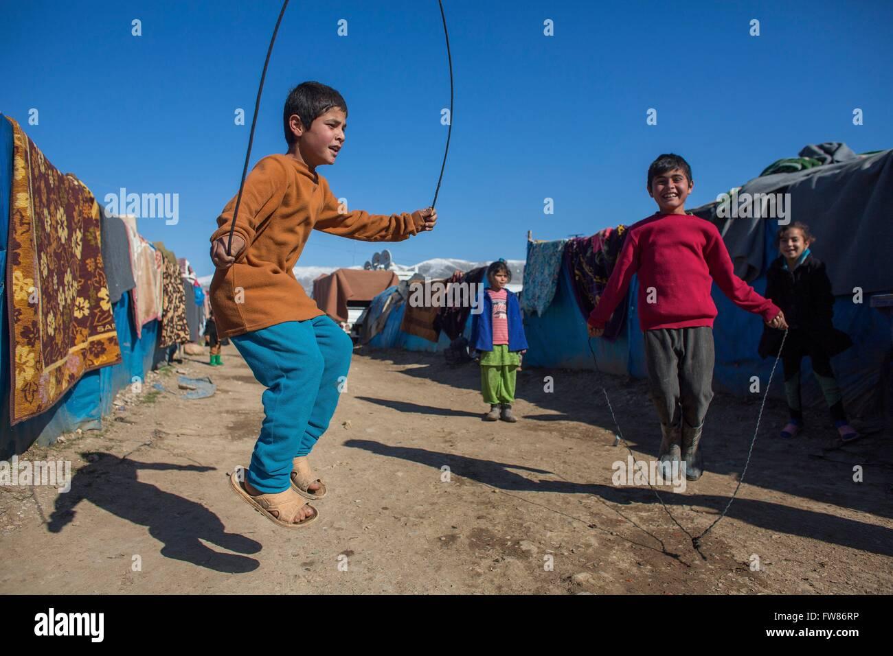 Los niños saltar la cuerda en un campamento de refugiados en el norte de Irak Imagen De Stock