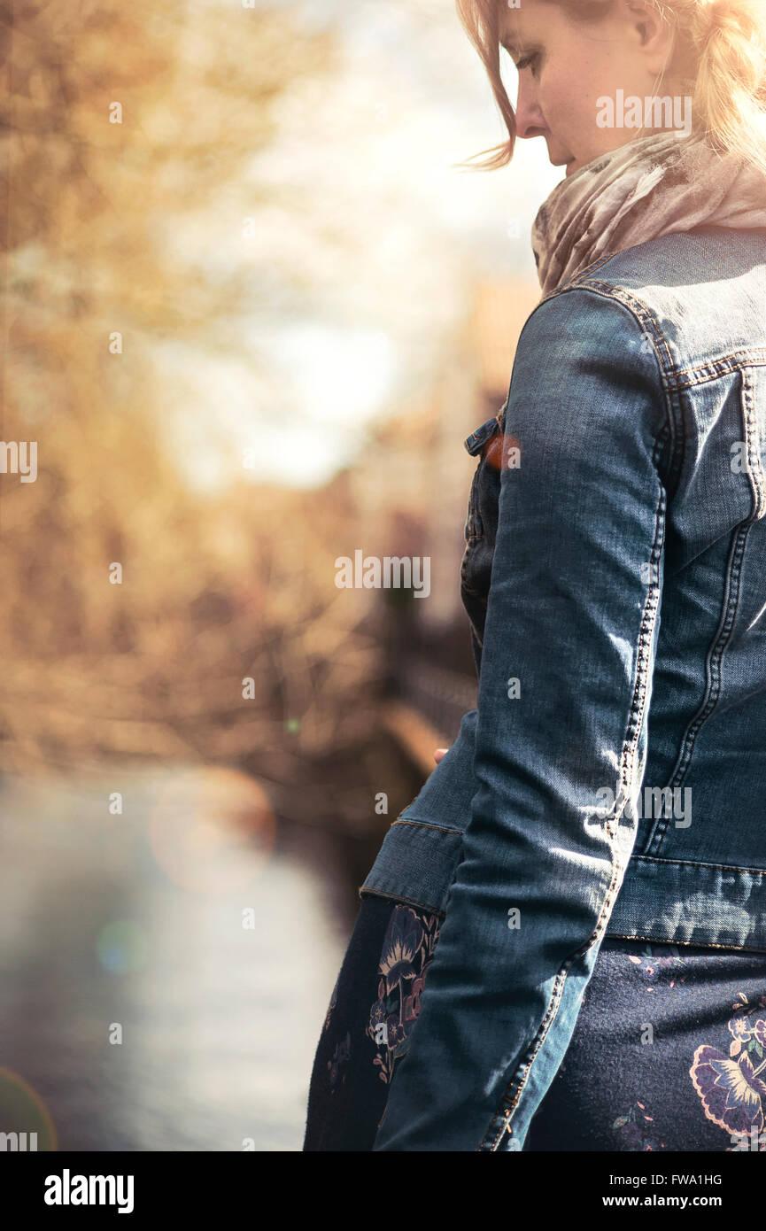 Vista posterior de la joven caminando a lo largo de la ruta Imagen De Stock