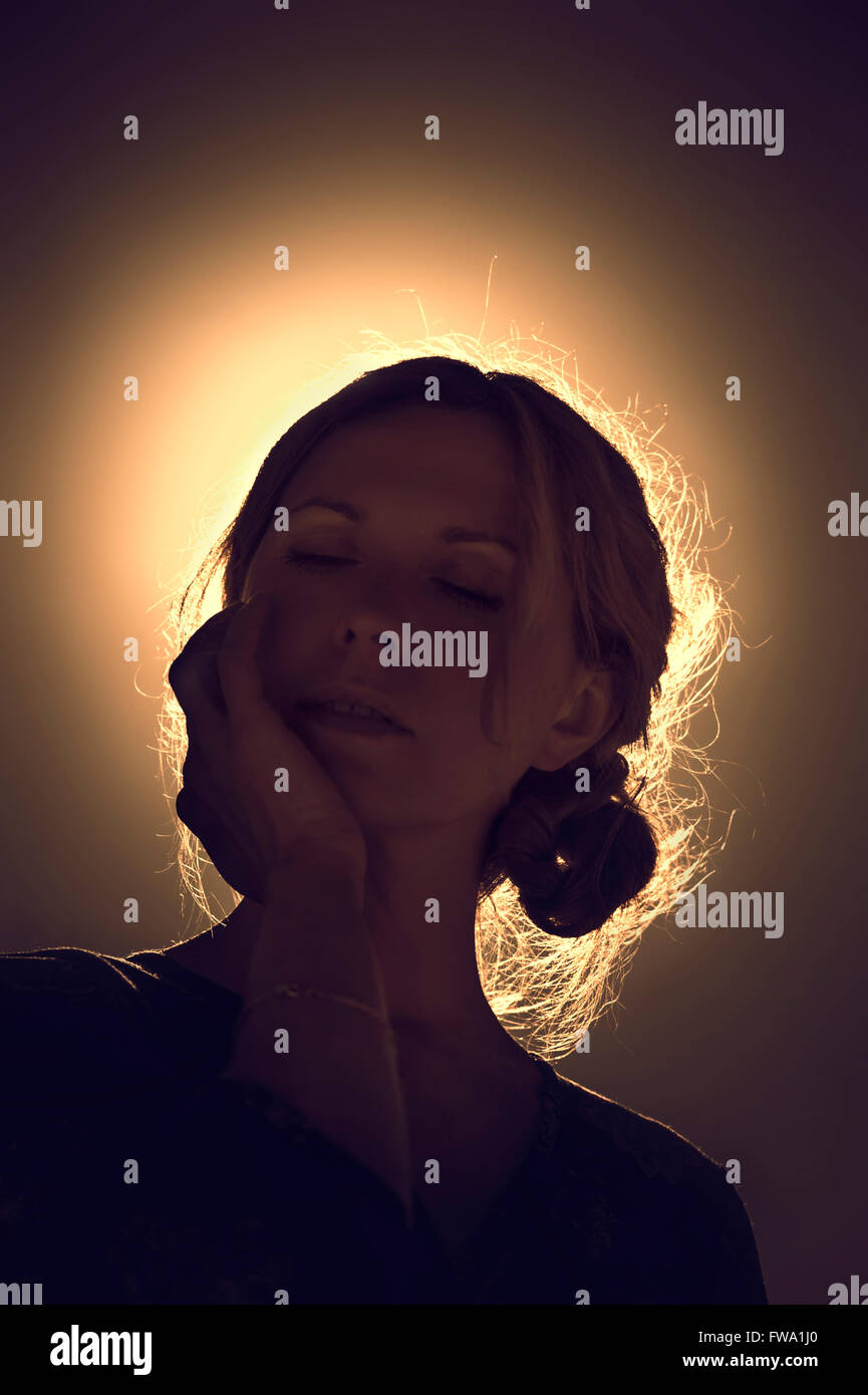 Retrato de mujer joven contra la luz del sol Foto de stock