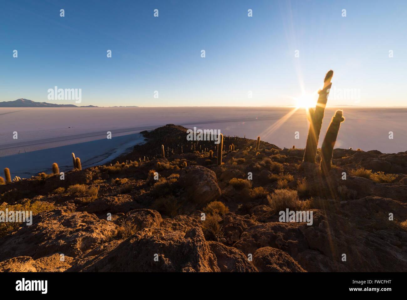 El sol en el horizonte del majestuoso Salar de Uyuni, uno de los destino más importante en Bolivia. Ancho Imagen De Stock