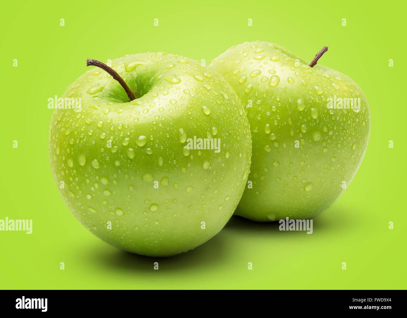 Manzana Verde fresco perfecto aislado sobre fondo verde en toda la profundidad de campo. Imagen De Stock