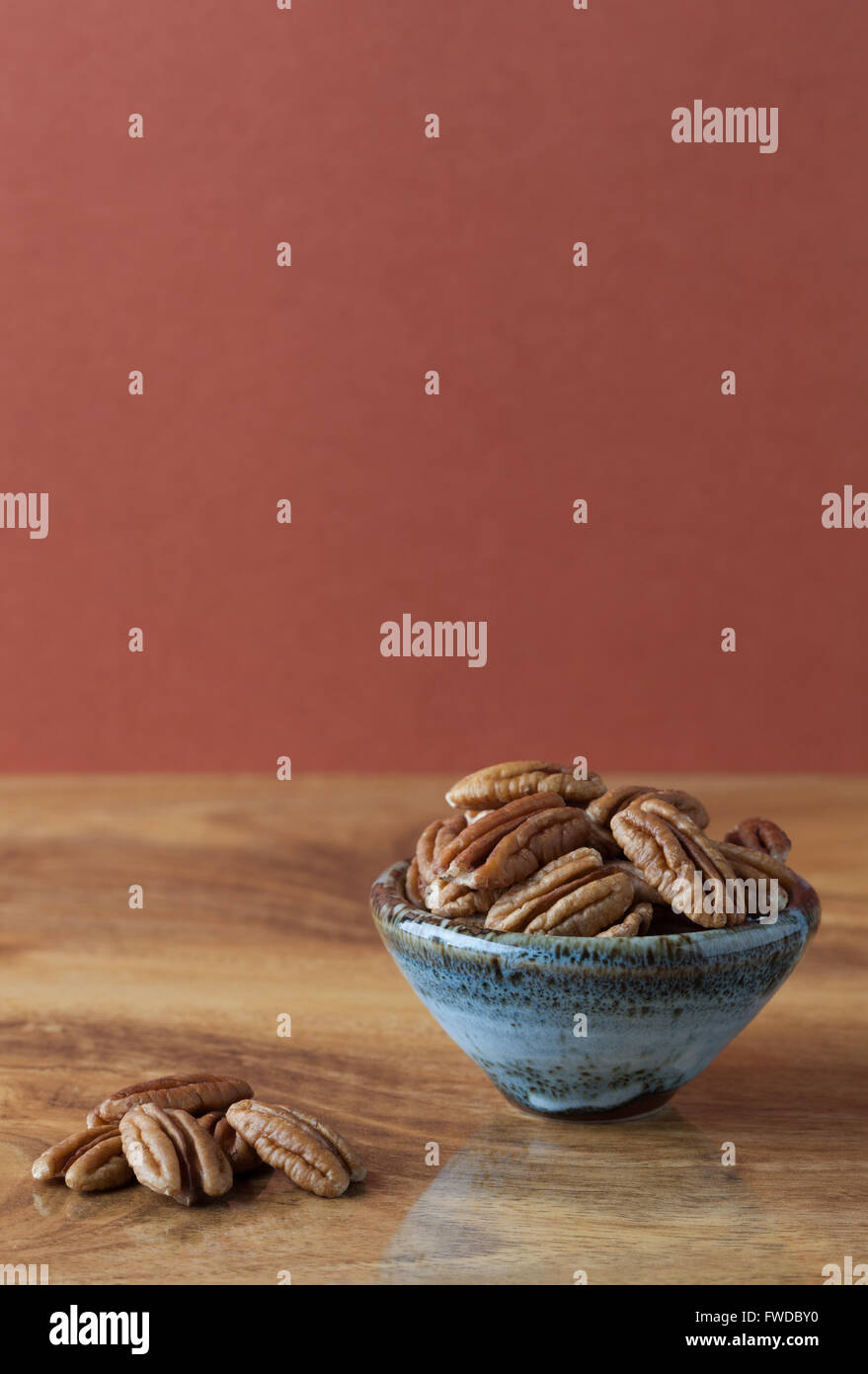La pacana sobre mesa de madera, y en el cuenco de cerámica con fondo marrón. Copie el espacio, profundidad Imagen De Stock