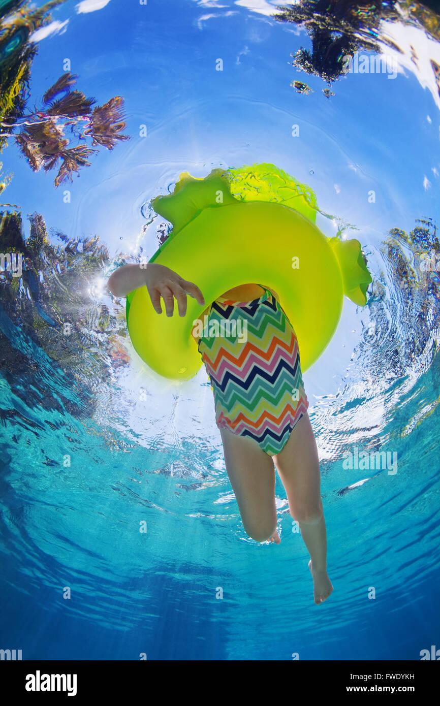 Gracioso foto submarina de niña a nadar con la diversión el tubo rana inflable en clara aqua park piscina. Estilo de vida familiar saludable. Foto de stock