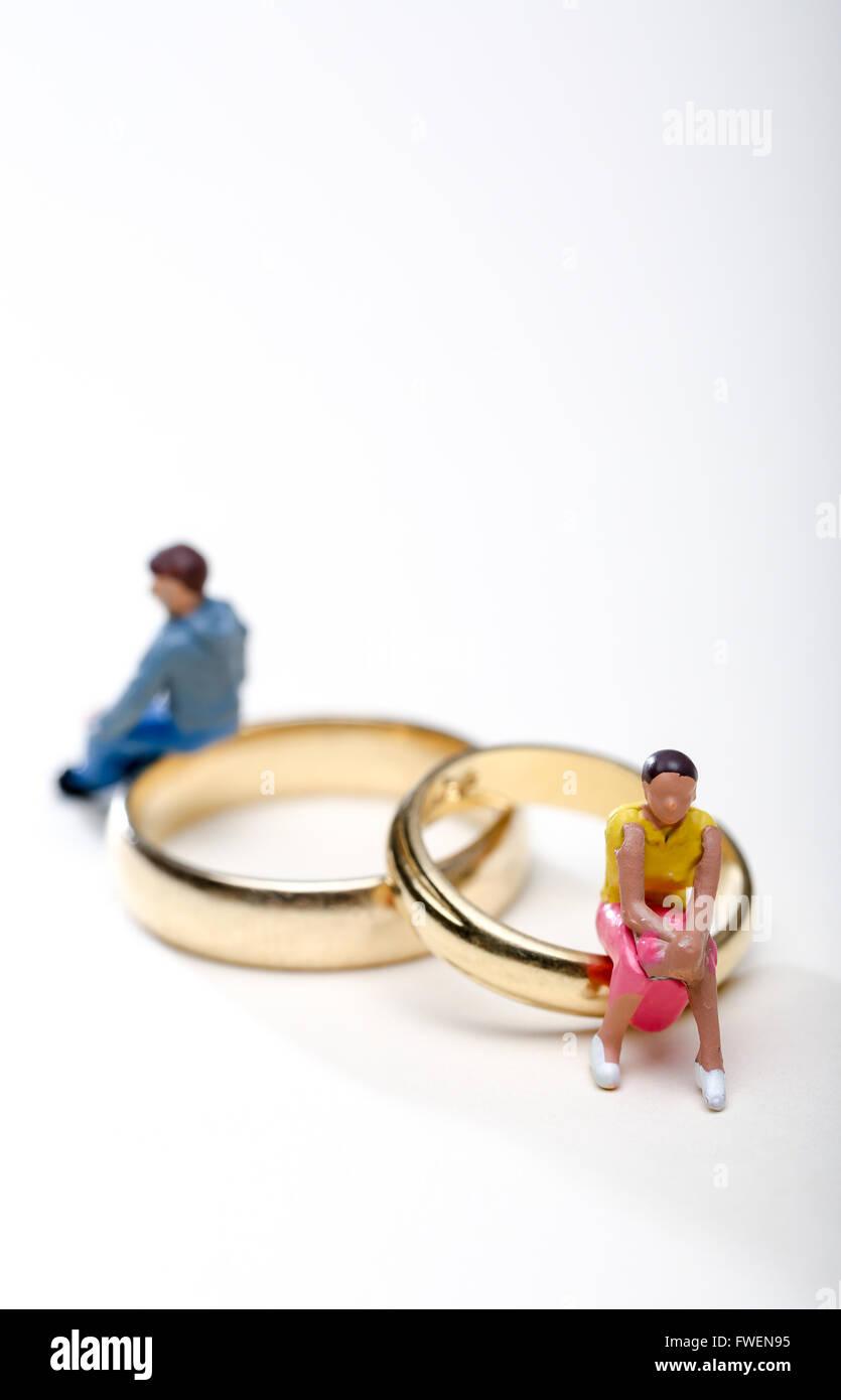Concepto de imagen una pareja se sentó sobre los anillos de bodas para ilustrar el divorcio y separación Imagen De Stock