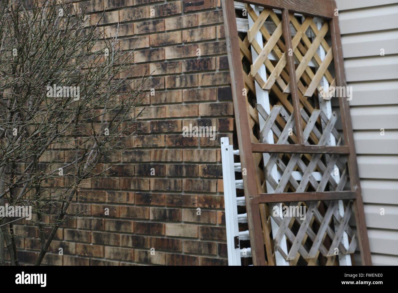Paneles de madera entrecruzadas se inclina contra una casa con paredes de ladrillo en invierno. Imagen De Stock