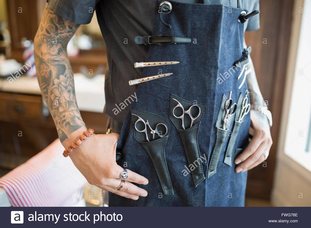 La mitad del torso tatuado barber vistiendo delantal con herramientas Imagen De Stock