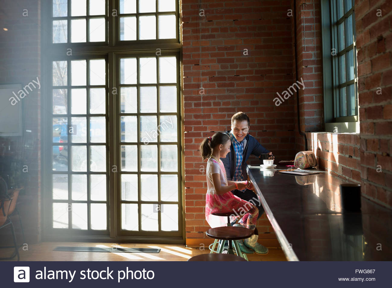 Padre e hija disfrutando de café en la cafetería. Imagen De Stock