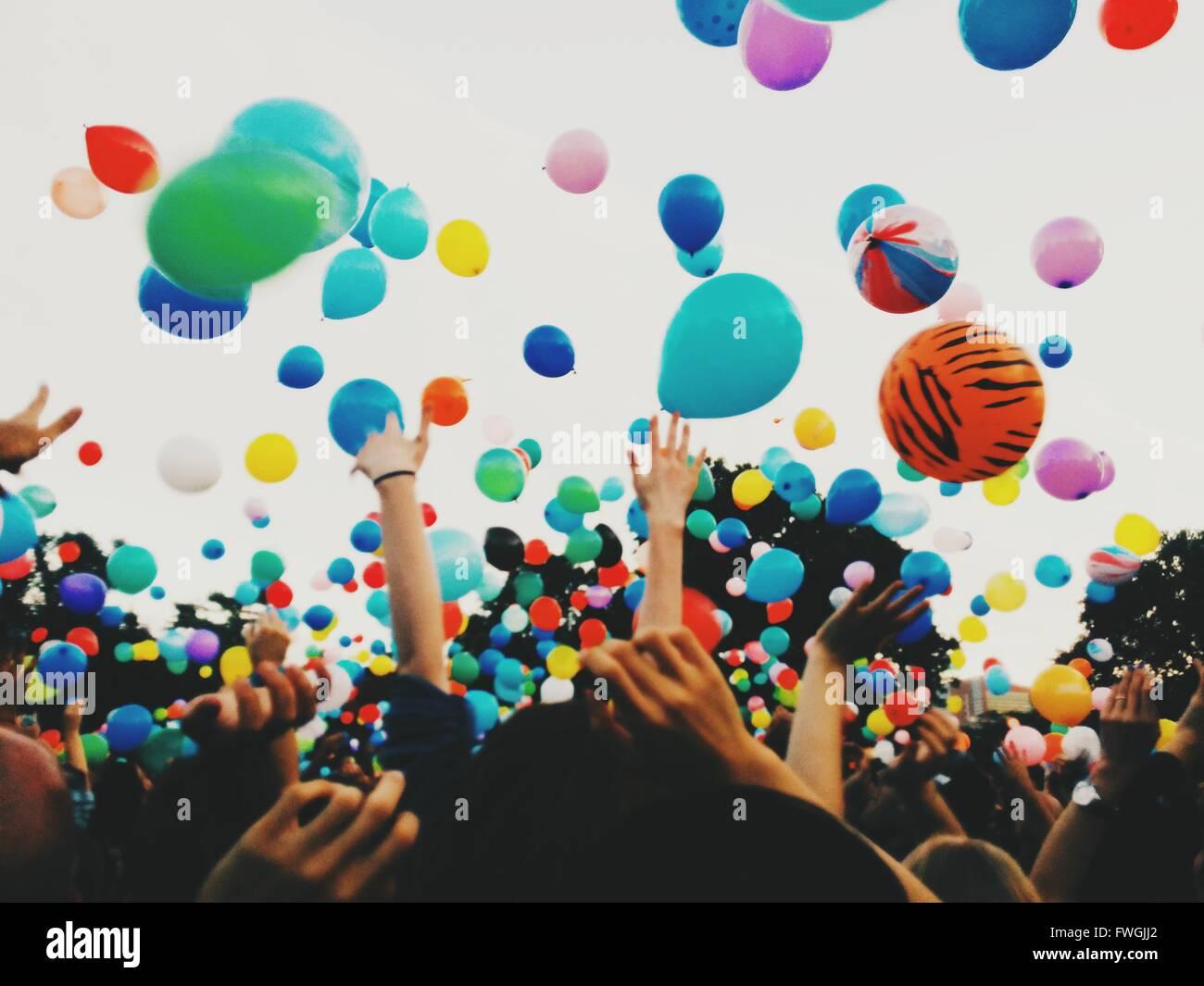 Multitud lanzando globos de colores contra el cielo durante el festival Imagen De Stock