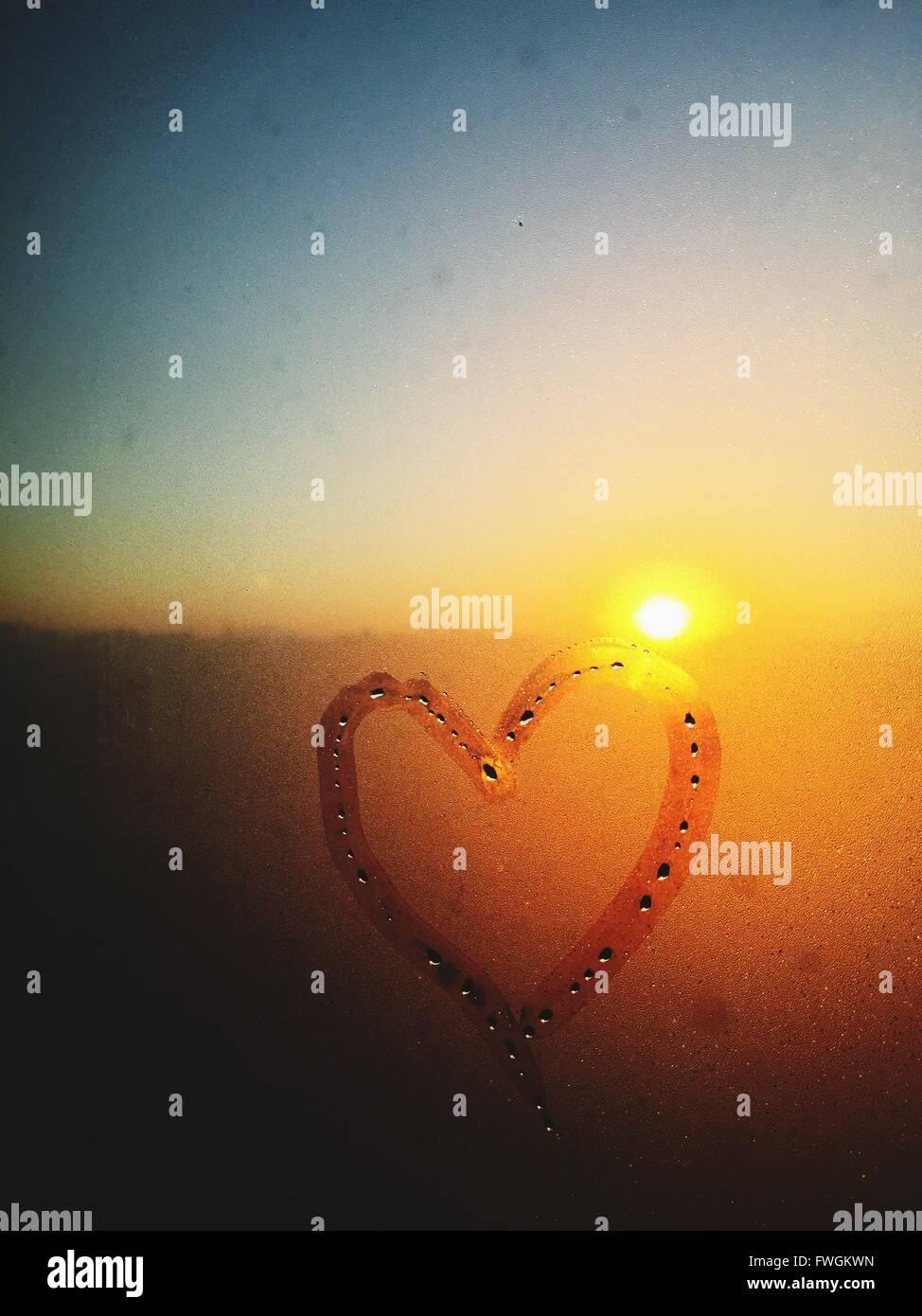 Corazón dibujado en la ventana condensada Foto de stock