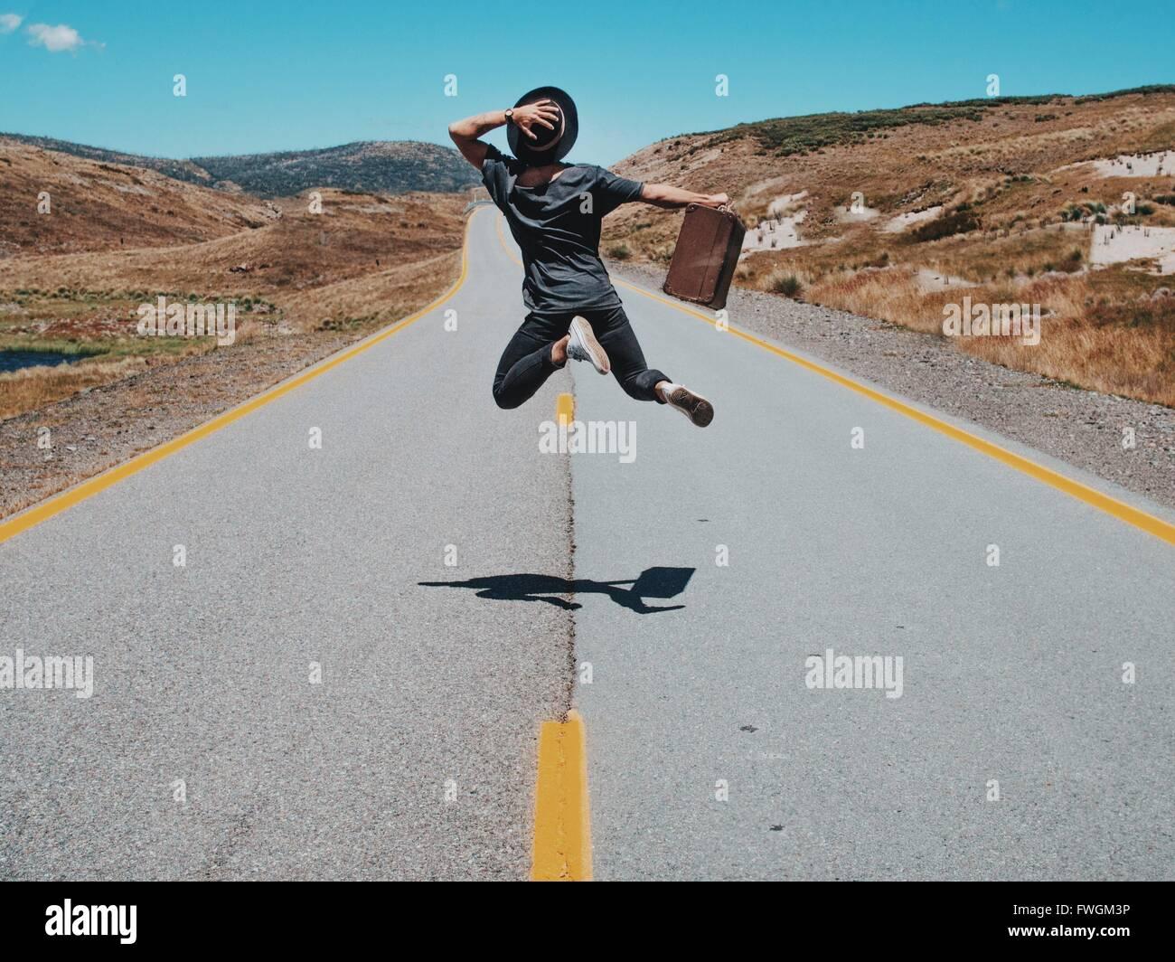 Vista trasera del hombre saltando sobre Country Road contra Sky Imagen De Stock