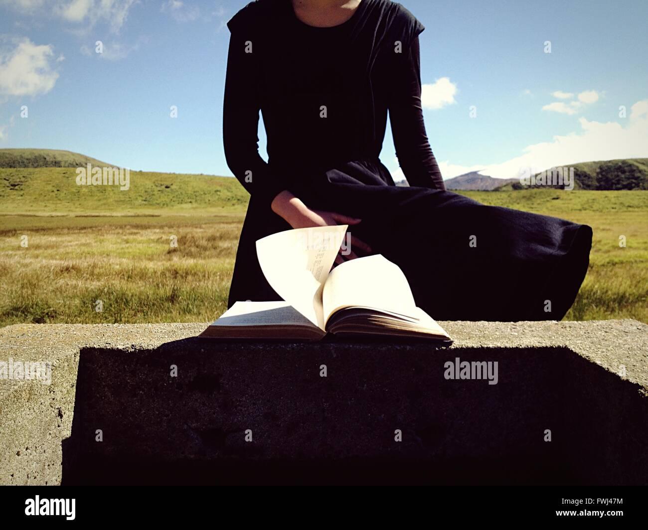 Sección media de la Mujer por el muro de retención con el libro Imagen De Stock