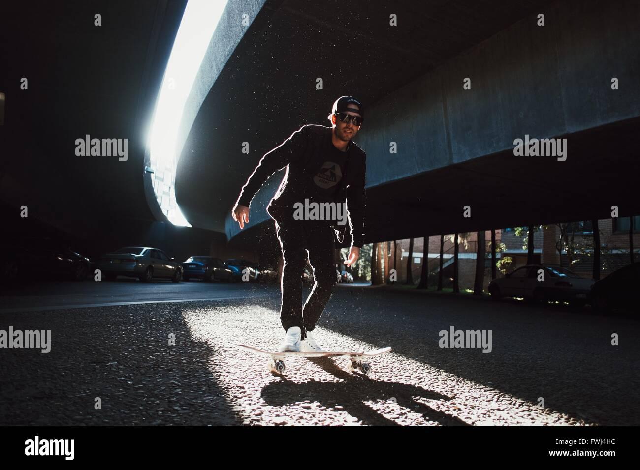 Hombre de pie sobre el monopatín Imagen De Stock