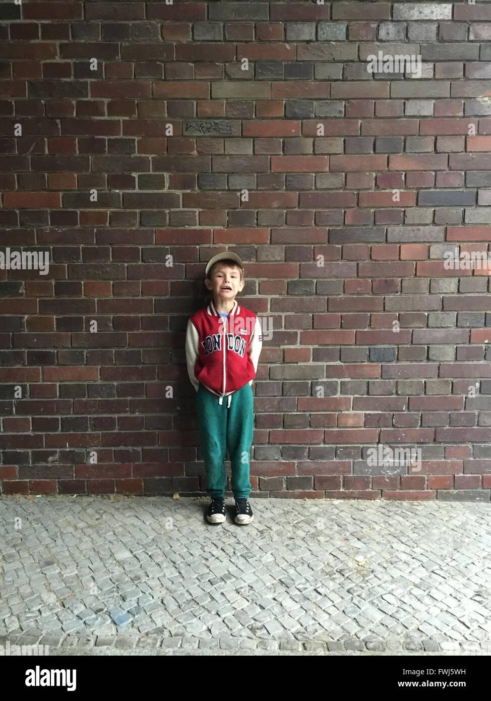 Retrato de niño llorando mientras está de pie contra la pared de ladrillo Imagen De Stock