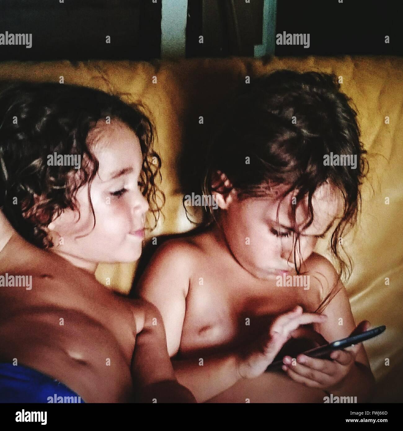 Ángulo de visión de alta de hermano y hermana jugando con Smart Phone en casa Imagen De Stock