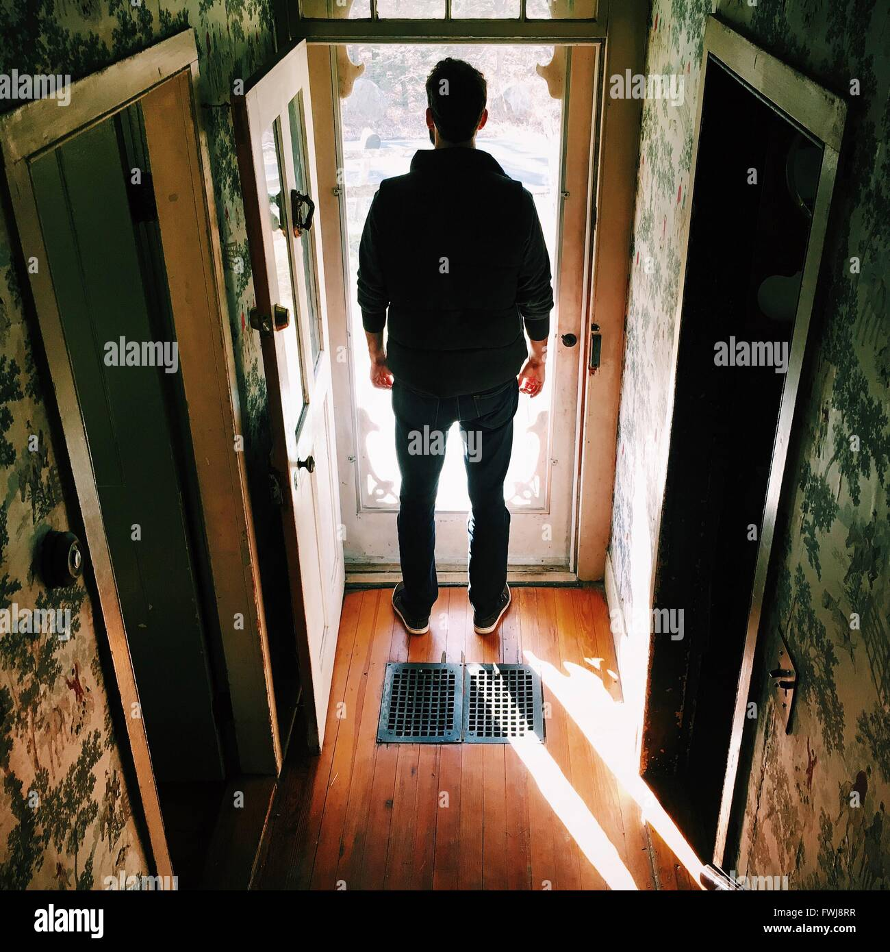 Vista trasera del hombre de pie en el umbral Imagen De Stock