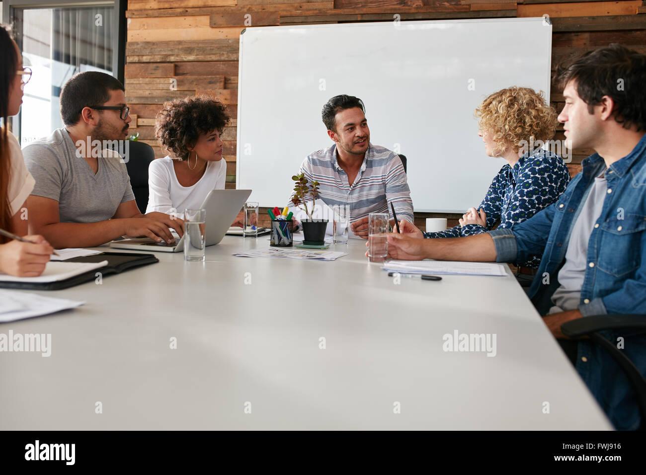 Retrato de los jóvenes trabajadores de oficina reunidos en una sala de juntas. Equipo de negocios multiétnico Imagen De Stock