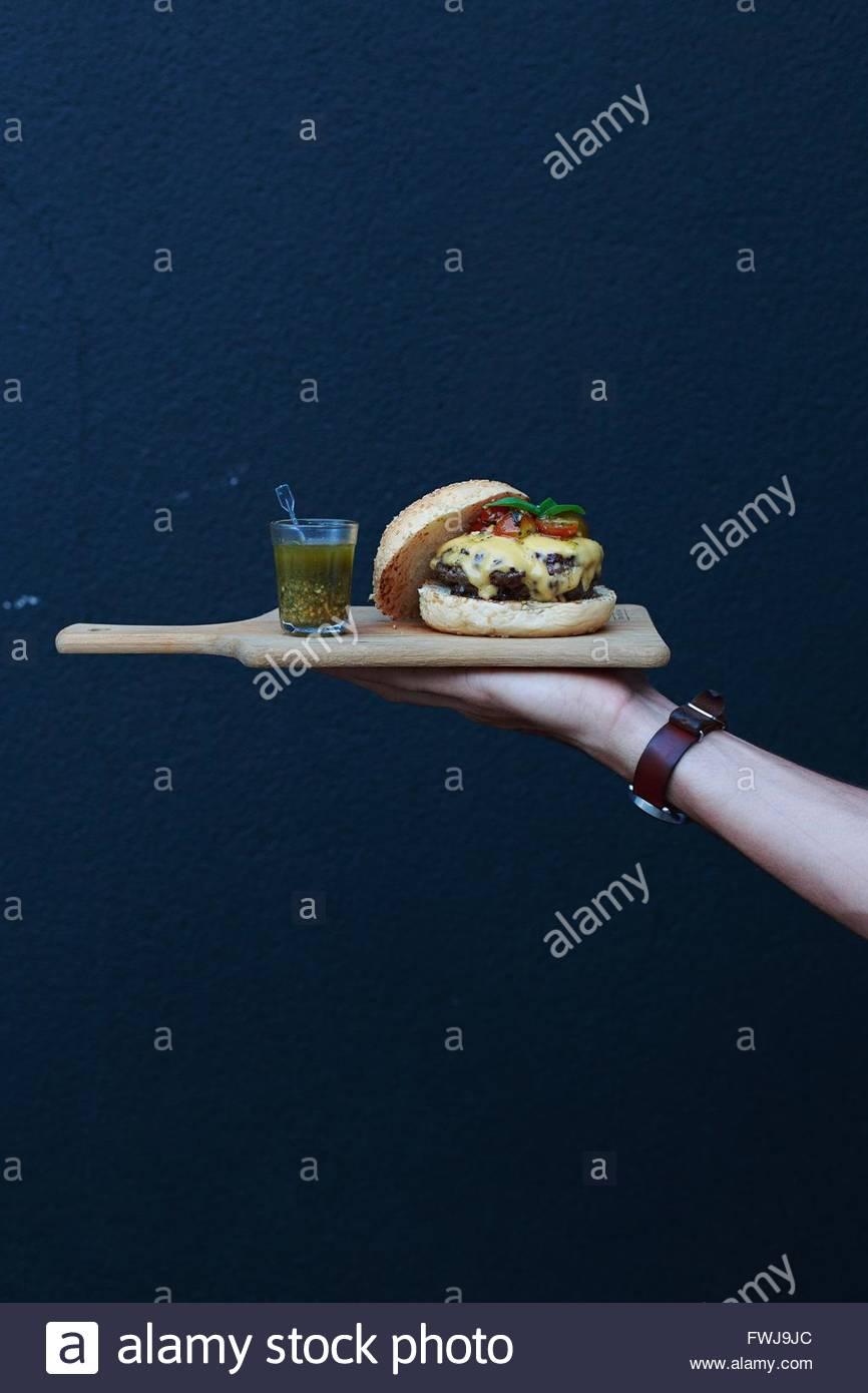 Recorta mano sujetando una hamburguesa y bebida en placa de corte contra la pared Imagen De Stock