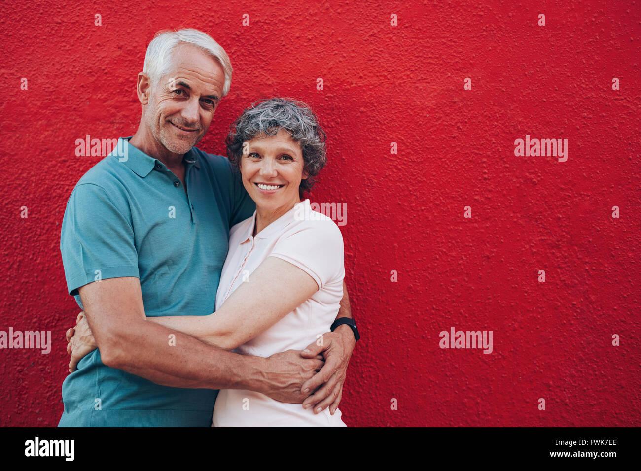 Retrato de amar al hombre y a la mujer de mediana edad de pie juntos contra el fondo rojo. Senior pareja abrazada Foto de stock