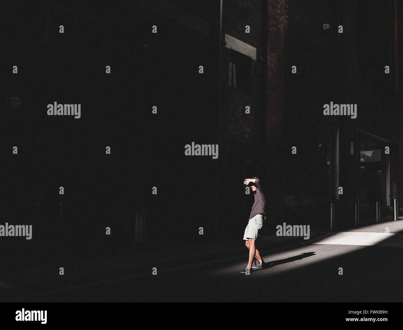 La longitud total del hombre de pie en la calle contra la construcción Imagen De Stock