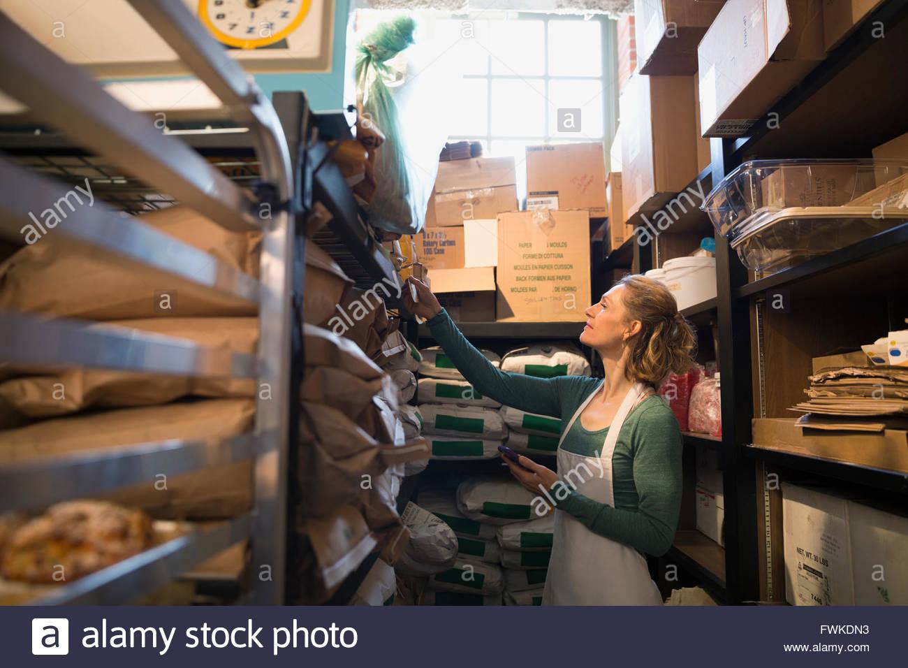 Propietario de la Panadería La comprobación del inventario de suministros en el trastero Imagen De Stock