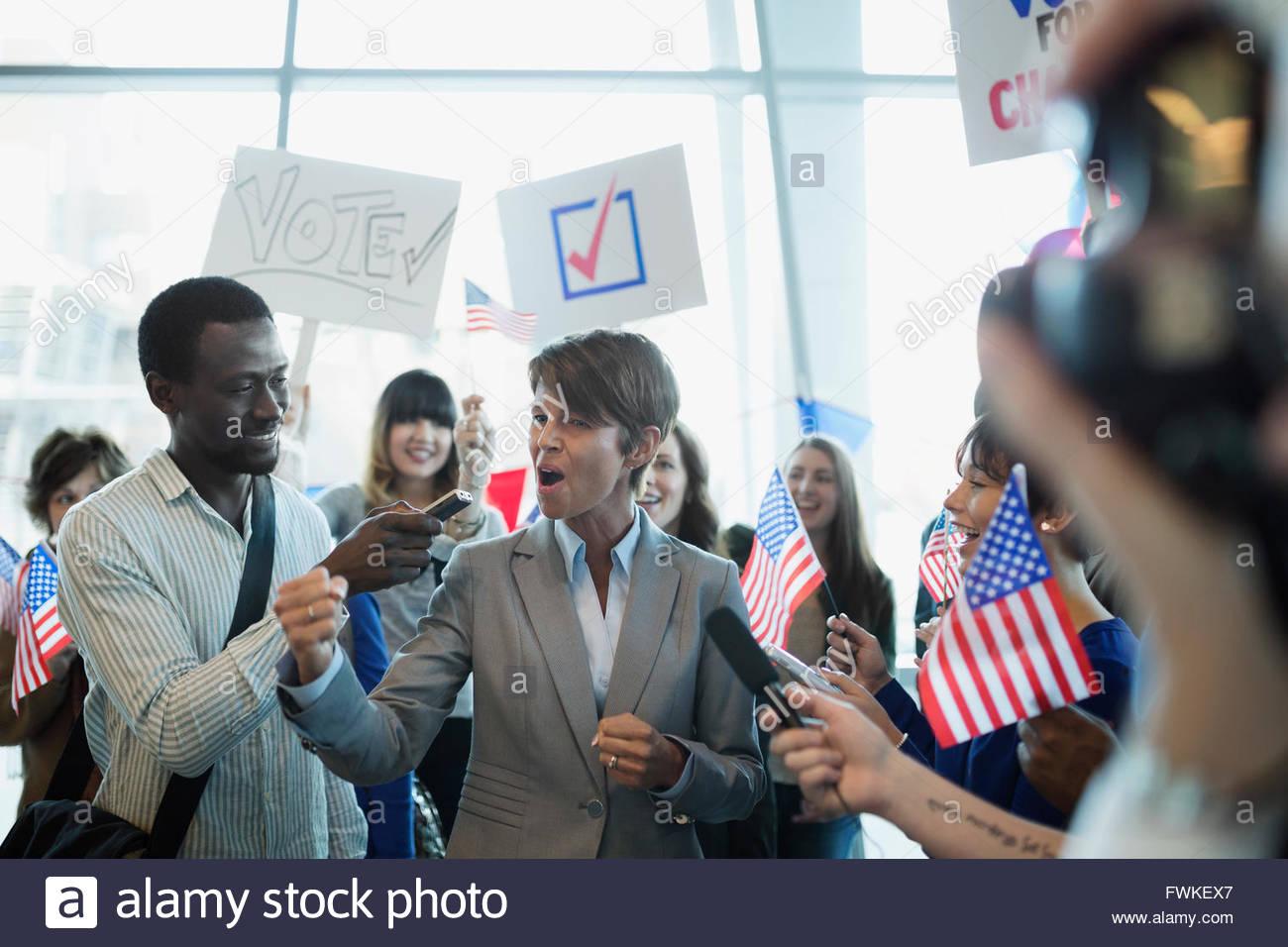 Vítores político femenino siendo entrevistado en mitin político Imagen De Stock