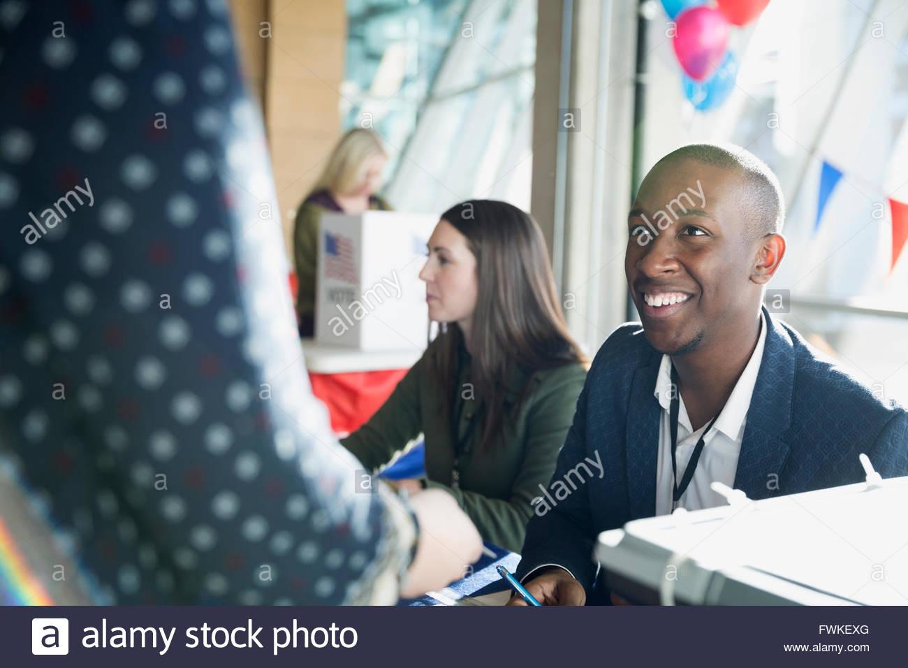 Control voluntario sonriente elector en polling place Imagen De Stock