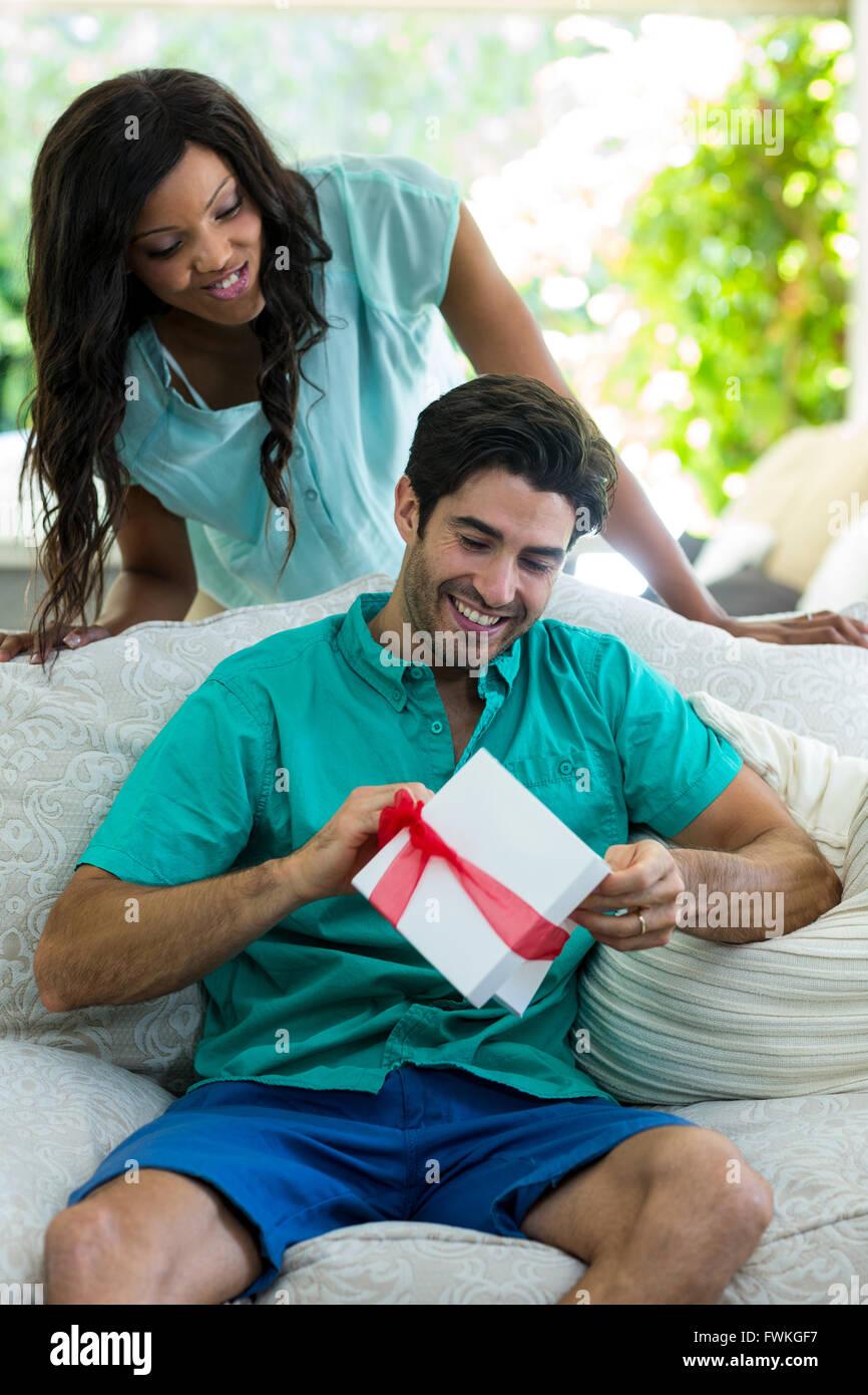 Mujer mirando un hombre que desenvolver un regalo Imagen De Stock