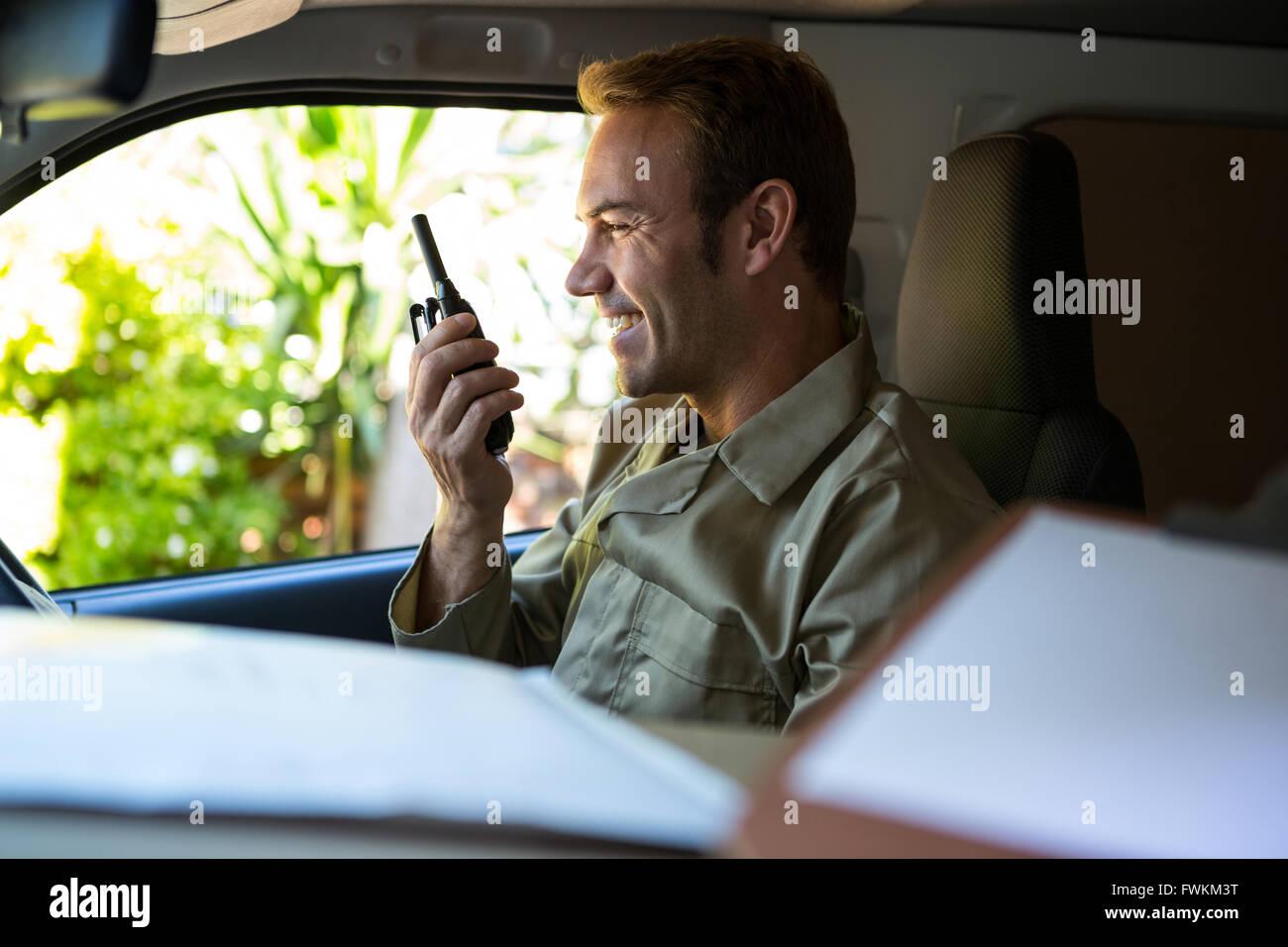 Controlador de entregas hablando por walkie-talkie Imagen De Stock
