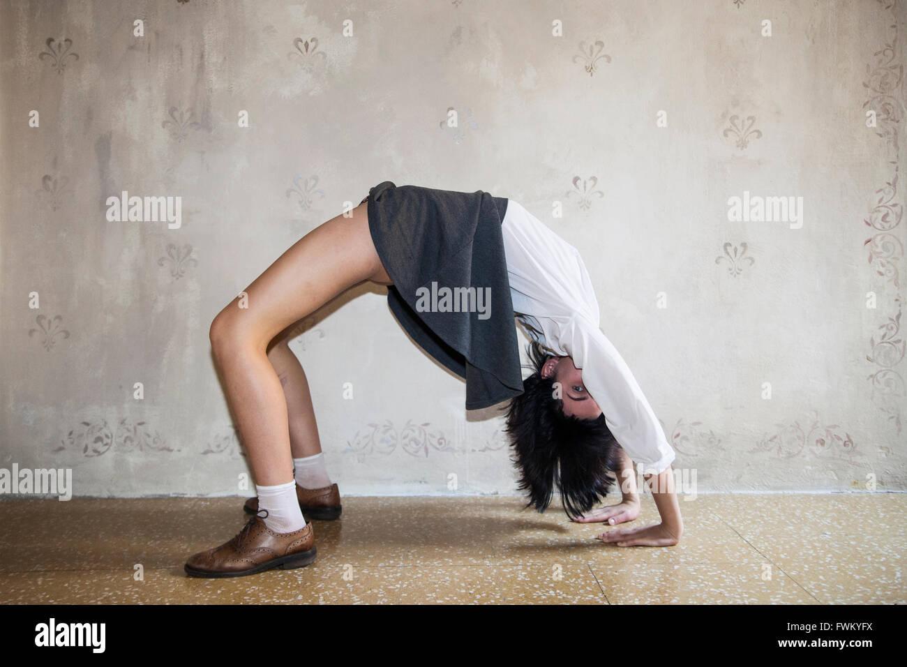La longitud completa de la mujer practicando Yoga contra la pared Imagen De Stock