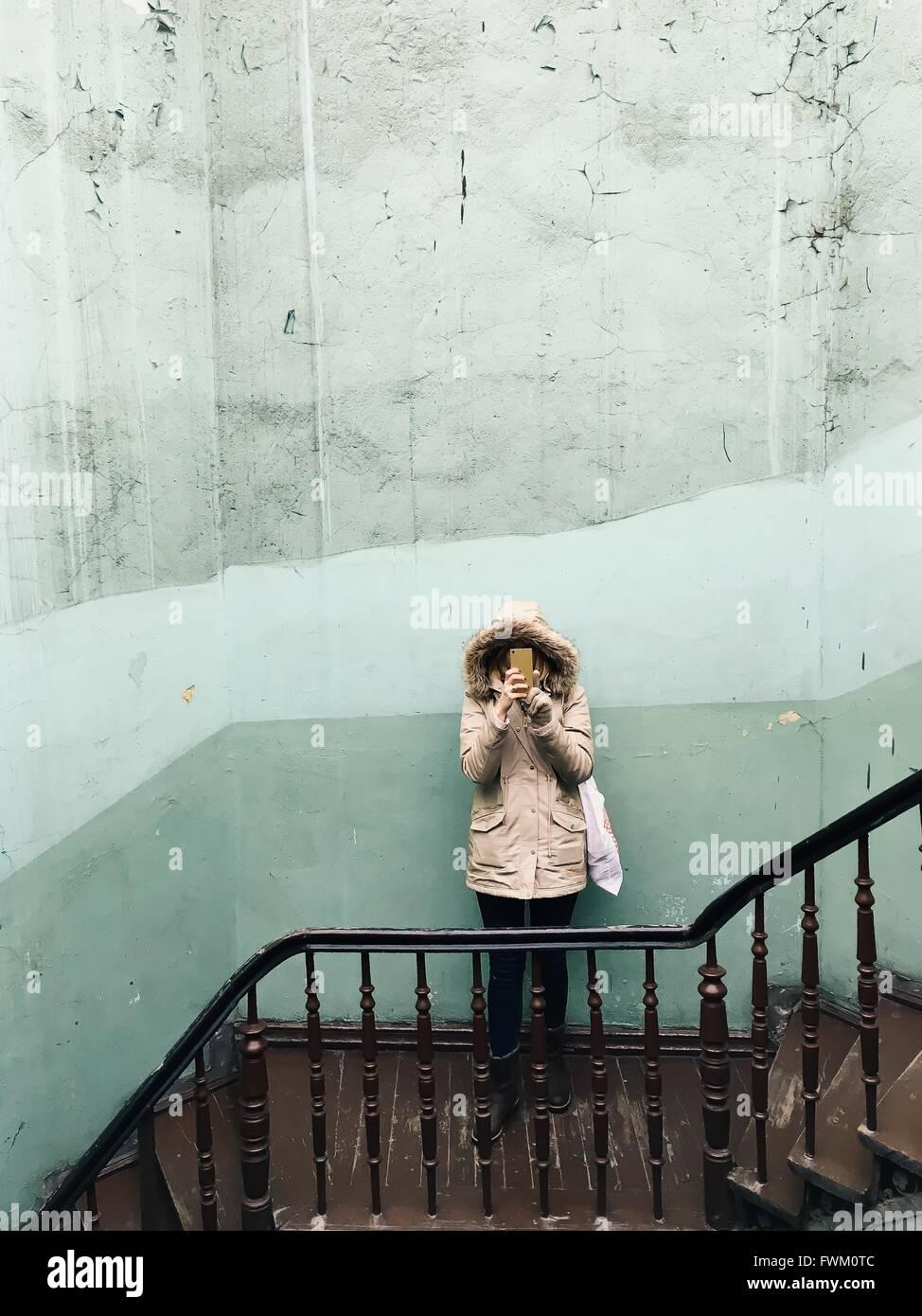 Un alto ángulo de visualización de la mujer sosteniendo teléfono inteligente contra la pared en pasos Imagen De Stock