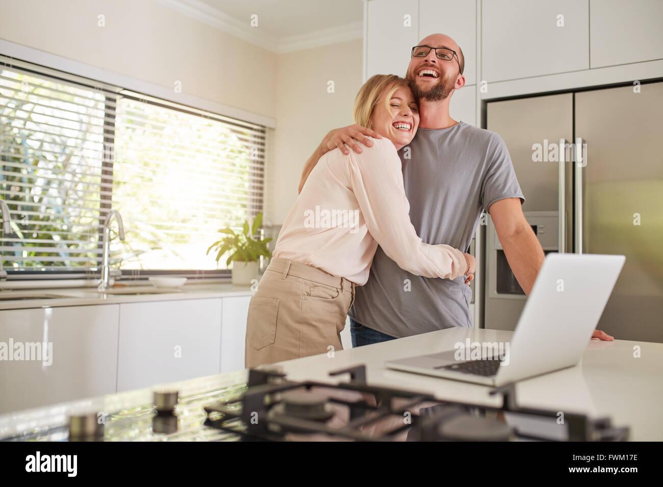 Retrato de mujer alegre y abrazando a su marido en la cocina. Pareja amorosa con el portátil en la cocina en Imagen De Stock