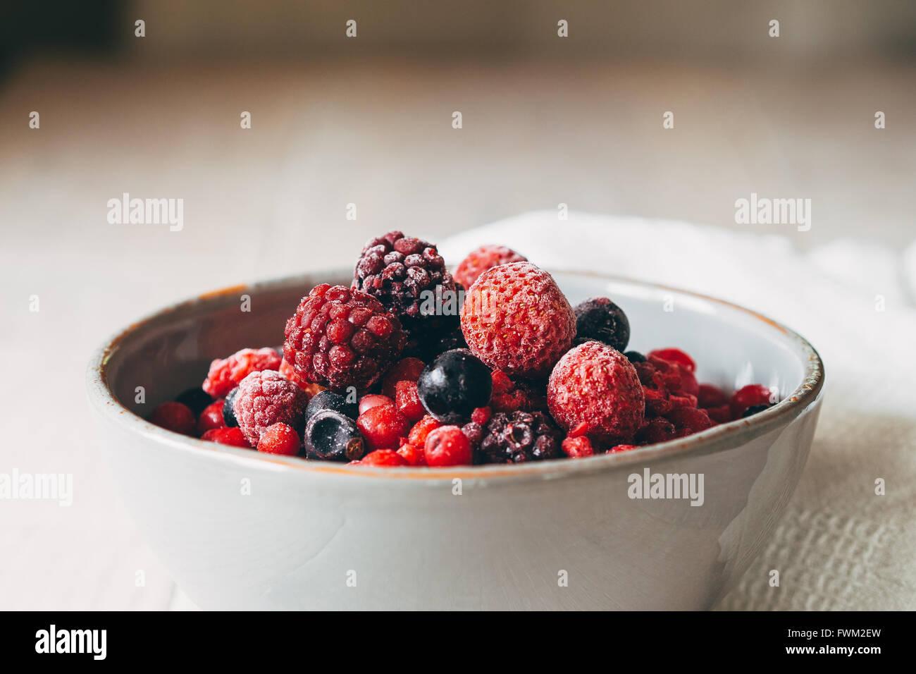 Primer plano de bayas en el tazón en la mesa Imagen De Stock