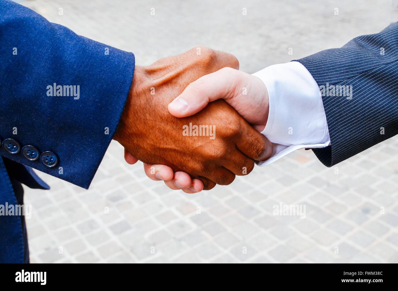 Primer plano de hombres haciendo apretón de manos al aire libre Imagen De Stock