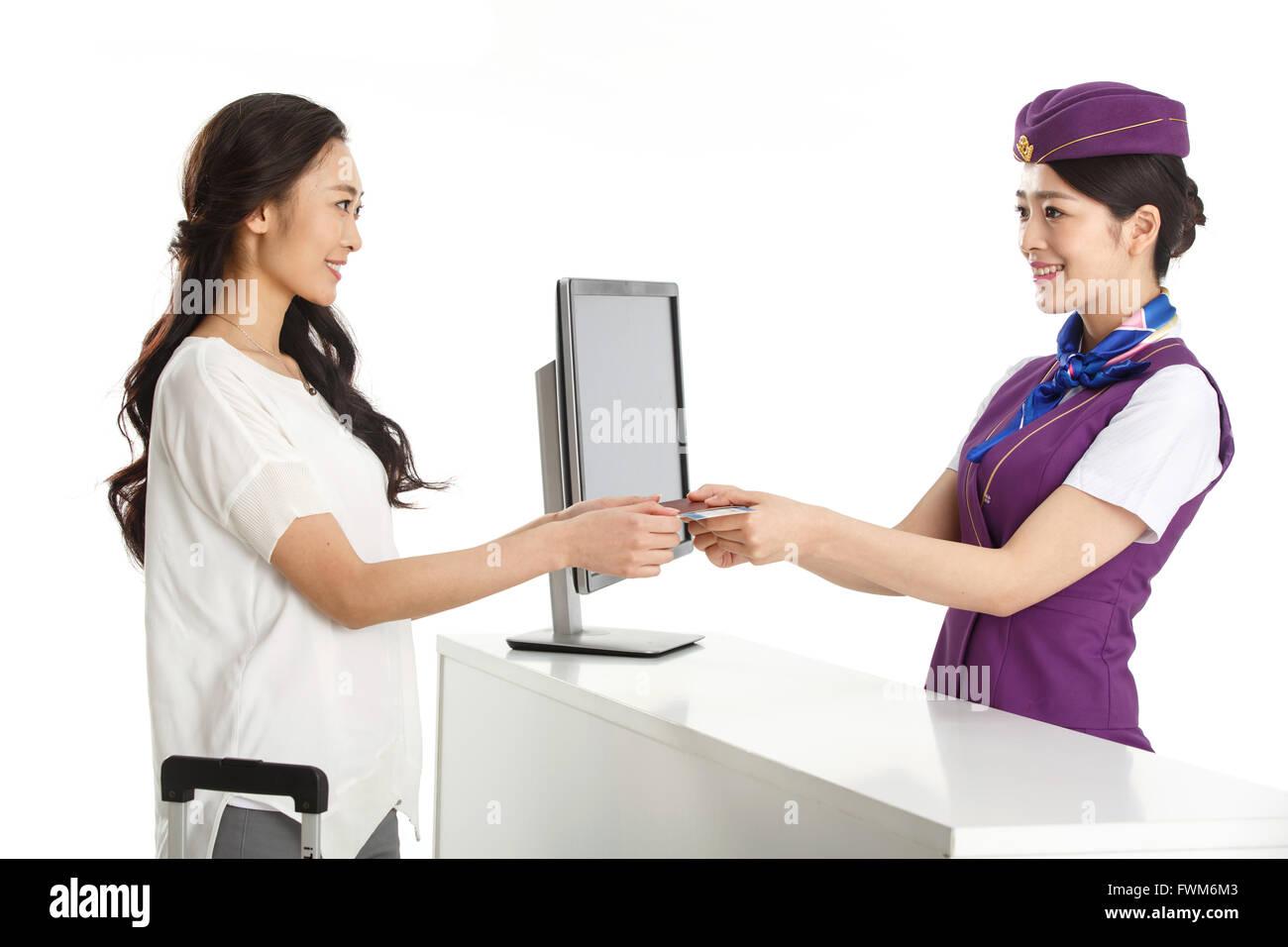 Las hembras jóvenes asistentes de vuelo para los clientes para pasar un pasaporte Imagen De Stock