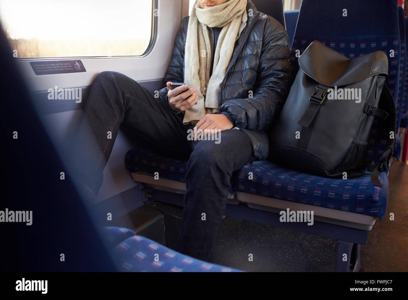 Hombre sentado en el tren transporte Enviar mensaje de texto Imagen De Stock